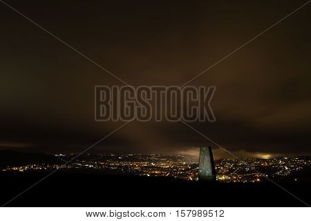Trig point on Little Solsbury Hill overlooking Bath. Night view of the UNESCO World Heritage City of Bath with stone used for cartographic triangulation in foreground