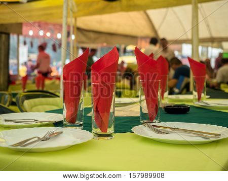 Picture of the dining-table served with red napkin. White plates with flatware and red napkin against the blurred background of the guests of a restaurant. Plates, flatware, glass and red napkin