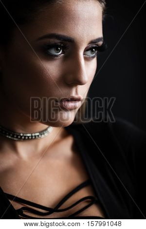 Closeup portrait of a young trendy agressive woman in bodysuit posing near black wall