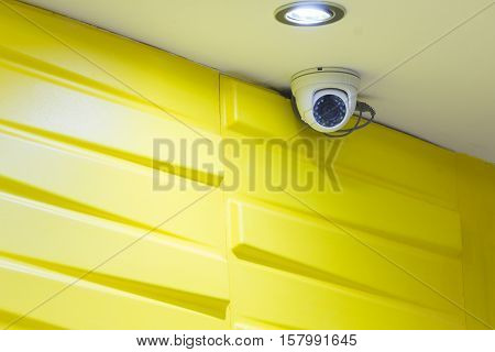 The CCTV security camera operating on luxury roof house with modern yellow wallpaper.