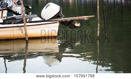 Picture of the fishing boat with outboard motor in the shallow river. Fishing boat with beige - coloured bottom anchoring on the river shore.