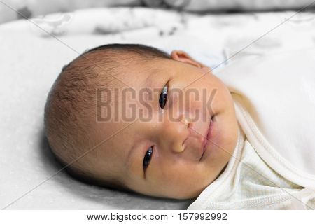 Asian cute new born baby sleeping on white towel.