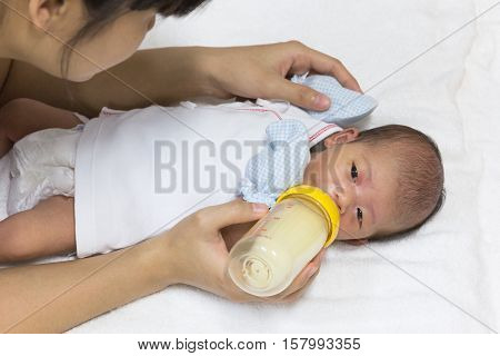 Asian cute new born baby eatting mlik mother in bottle mum feeding on white towel background.
