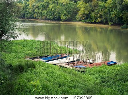 Picture of the landscape scene in the forest. With old fishing boats on the near river-bank and depths of a green forest on the far bank. Green grass covered a shore of the river.