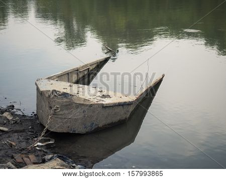 The landscape scene of the halfsunken fishing boat. . An old dirty halfsunken boat attached to the shore with rusty chain . A river slick reflect the green trees.