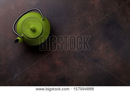Green tea pot on stone table. Top view with copy space