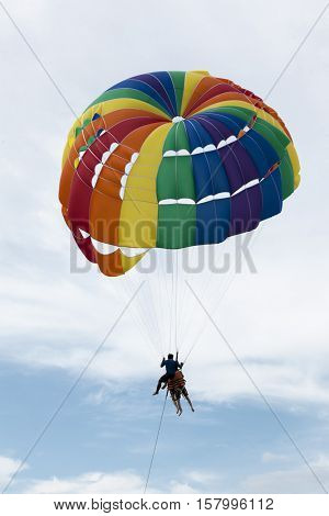Two Chinese tourists flying on a parachute over the sea on a beach in Phuket Thailand. Beautiful color large parachute in the blue sky tropical beach.