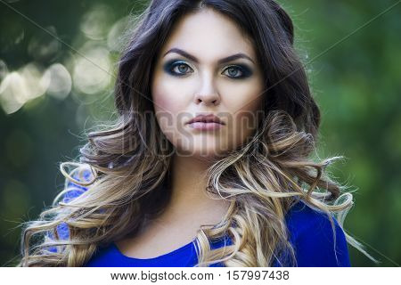 Young beautiful plus size model in blue dress outdoors confident woman on nature professional makeup and hairstyle close-up portrait sunbeams background
