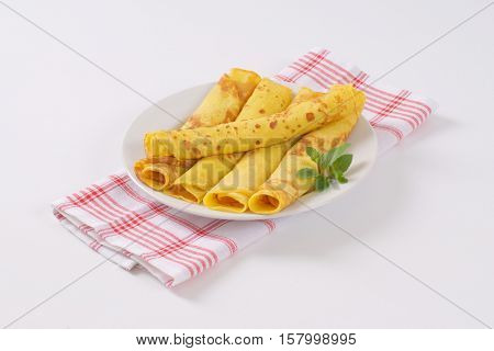plate of empty rolled pancakes on checkered dishtowel