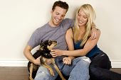 Attractive young couple sitting in their new home with their dog poster