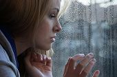 sad young woman looking through window on rainy day. depression concept. poster