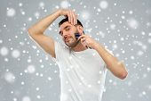 beauty, grooming, winter, christmas and people concept - smiling young man shaving beard with trimmer or electric shaver over snow on gray background poster