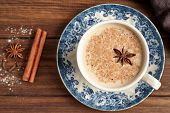 Masala tea chai latte traditional hot Indian sweet milk with spices, cinnamon stick, herbs blend organic infusion healthy beverage in porcelain cup on wooden table background poster