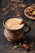 Masala pulled tea chai latte tasty hot Indian sweet milk spiced drink, ginger, fresh spices and herbs blend, anise organic infusion healthy wellness beverage teatime ceremony in rustic clay cup poster