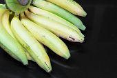 Cavendish bananas on black granite table background. poster