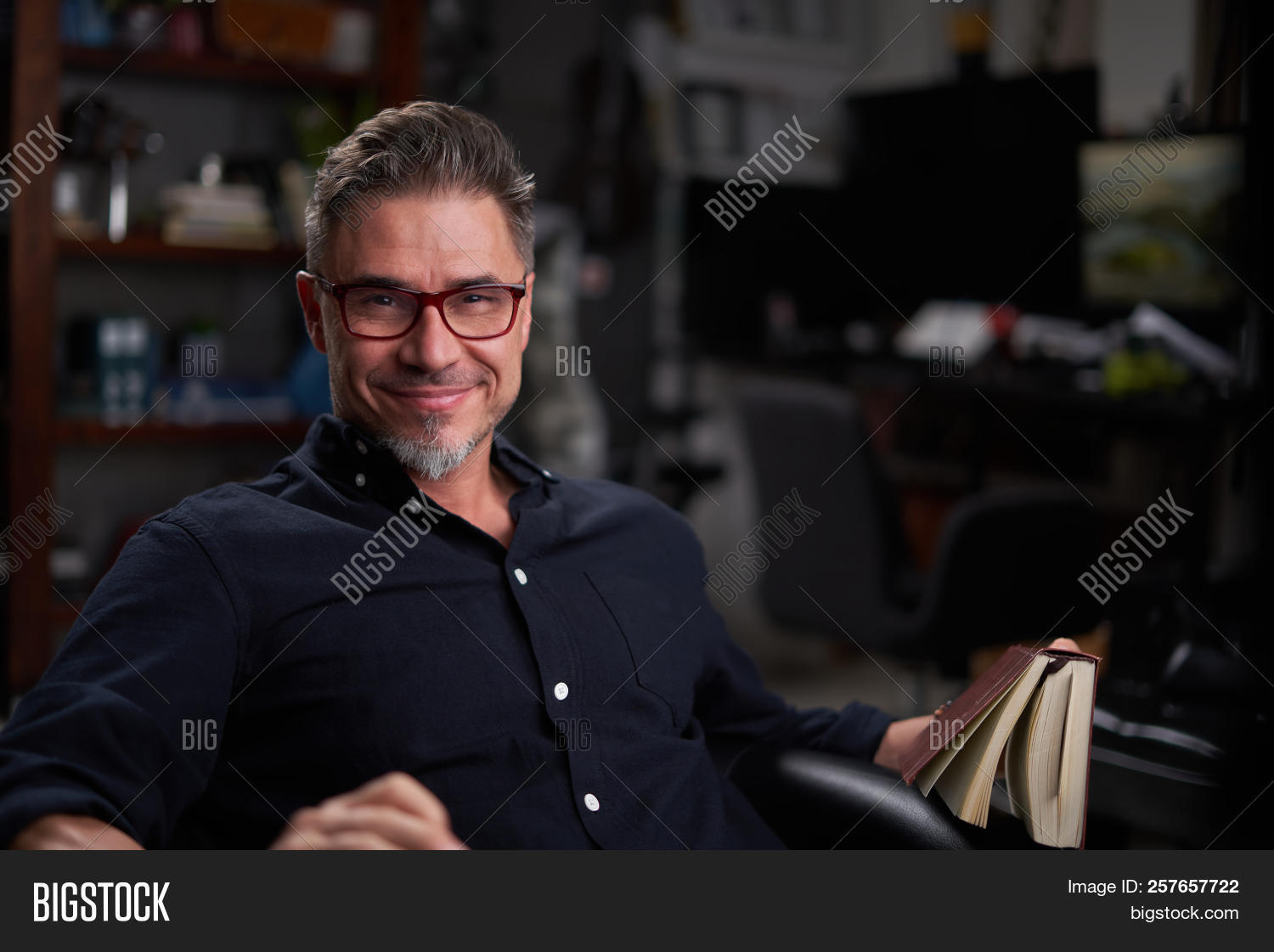 130ed117e4a9 Portrait of a good-looking happy older white man in glasses sitting reading  book at