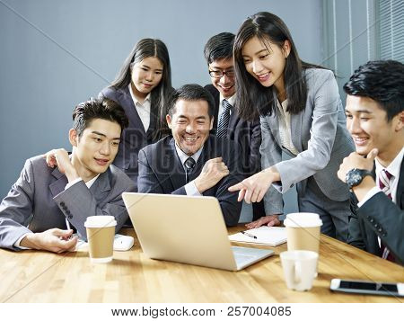A Team Of Asian Business Executives Working Together In Office Using Laptop Computer, Happy And Smil