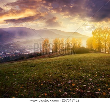 Cloudy Sunrise In Mountains. Gorgeous Countryside In Autumn. Trees With Yellow Foliage On Hill And F