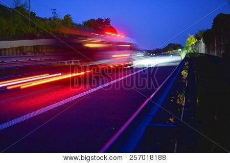 Evening Shot Of Trucks Doing Transportation And Logistics On A Highway. Highway Traffic - Motion Blu