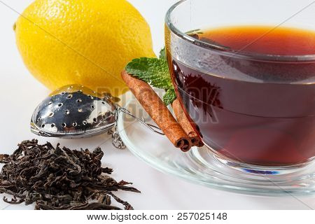 A glass cup with black tea on a saucer with mint, cinnamon and lemon, as well as a tea filter and tea leaves. Close-up. poster