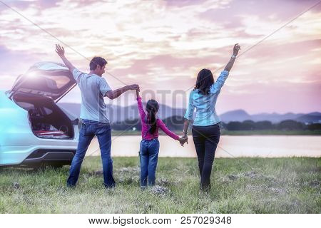 Silhouette The Happy Family Of Three People, Mother, Father And Child In Front Of A Sunset Sky; Asia