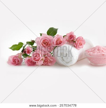 pink rose blossoms with rolled towel,salt in bowl on white background