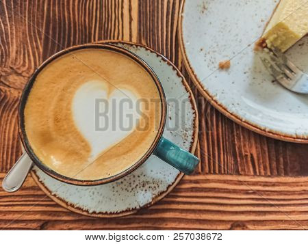 Cup Of Cappuccino With Latte Art And A Cheesecake Near It On A Brown Wooden Background. Stylish Foam