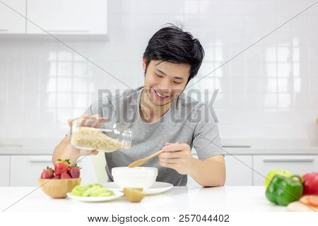 Attractive Handsome Young Guy Pour Cereal From Glass Bottle To Bowl For Making Breakfast In Morning.