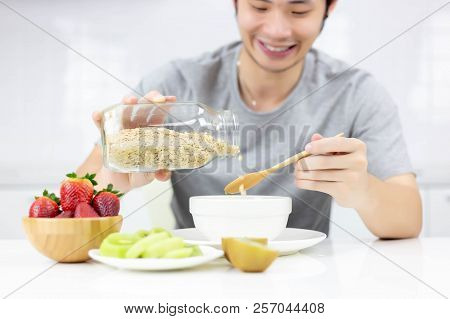 Attractive Handsome Young Guy Pouring Cereal From Glass Bottle To Bowl For Making Breakfast In The M
