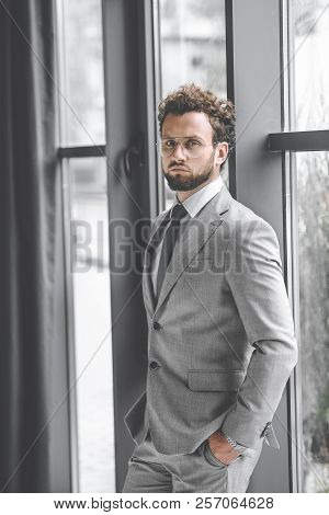 Confident Businessman In Suit With Hands In Pockets Looking At Camera