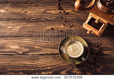 Wooden Background With Green Cup Of Coffee, Beans And Coffee Grinder. Top View. Retro Style Toned Da