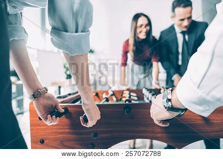 Close-up Shot Of Multiracial Businesspeople Playing Table Football In Modern Office