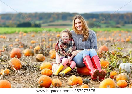 Little Kid Girl And Beautiful Mother Having Fun With Farming On A Pumpkin Patch. Traditional Family