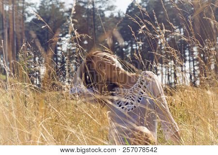 Lifestyle portrait of a beautiful woman in meadow. Beautiful woman in meadow. Healthy lifestyles. Beautiful people. People. Lifestyles concept. Young beautiful woman sitting in meadow. Beautiful woman relaxing in meadow. Beautiful woman in nature. Beautif