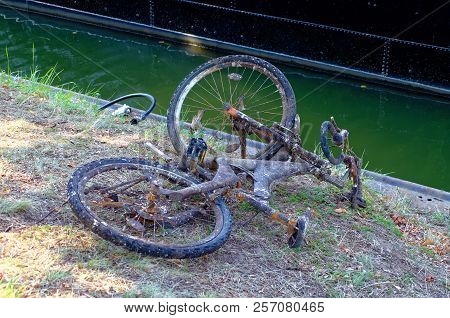 Old Rusty Bike Thrown In A River To Illustrate Illegally Disposed Garbage In Rivers And In The Sea