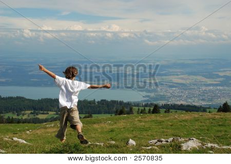 Child Jumping For Joy In Mountains With Landscape In Background