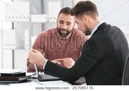 Businessman consulting young man in office