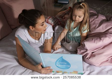 Mother reading bedtime story to her little daughter at home poster