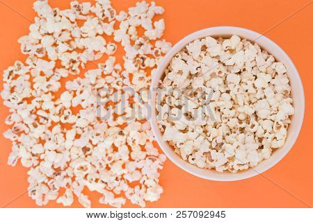 Paper Cup With Popcorn, And Popcorn Scattered On A Orange Background, Top View, Copyspace. Flat Lay.