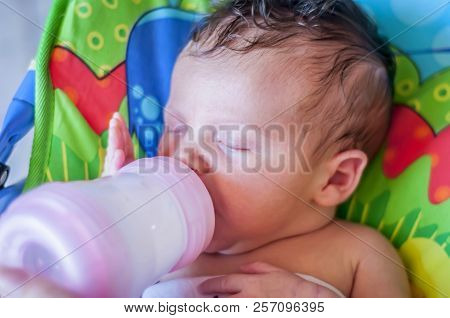 A Cute Caucasian Infant Child Eating Baby Food Infant Formula. Baby Formula Concept Image. Baby Bott