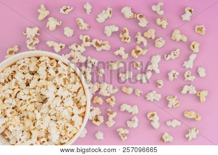 Paper Cup With Popcorn, And Popcorn Scattered On A Pastel Pink Background, Top View, Copyspace. Flat