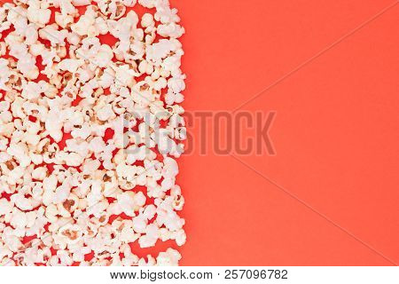 Popcorn Scattered At Half The Red Background Background And A Space For Copyspace. Popcorn On A Red