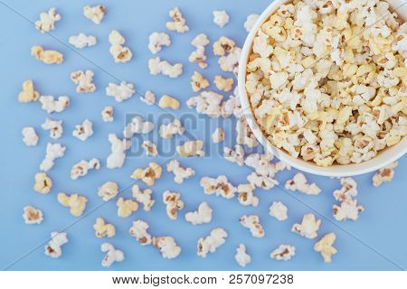 Paper Cup With Popcorn, And Popcorn Scattered On A Pastel Blue Background, Top View, Copyspace. Flat