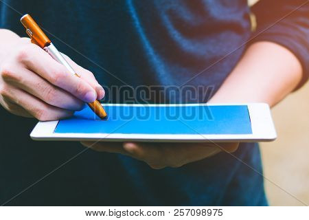 Background Of Financial Planning And Investment Concept. Young Man Holding And Writing On Blank Scre