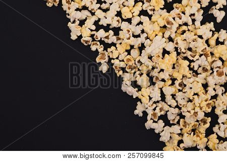 Popcorn Scattered At Half The Dark Background And A Space For Copyspace. Popcorn On A Black Backgrou