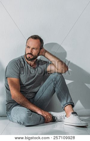 Full Length View Of Depressed Bearded Middle Aged Man Sitting And Looking Away