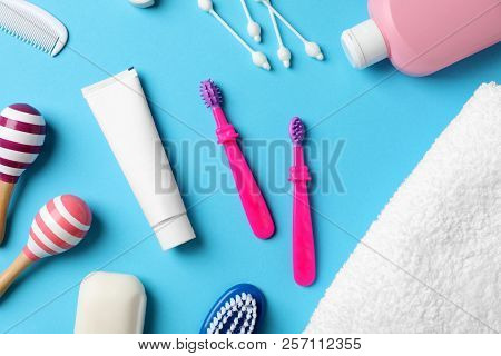 Flat lay composition with baby toothbrushes and toiletries on color background poster
