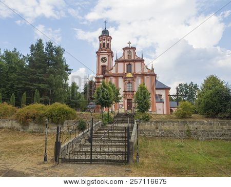 Pink and white baroque church of saint Mary Magdalene in Marenice, Czech Republic, sunny summer day, vibrant color poster