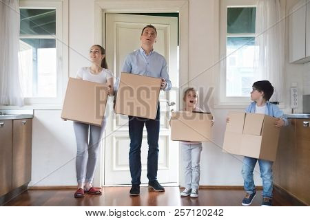 Impressed Family Carrying Boxes Moving In To New House