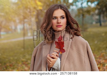 Cheerful Autumn Woman With Long Healthy Hair Holding Red Maple Leaf Outdoors In Sunny Day. Beautiful